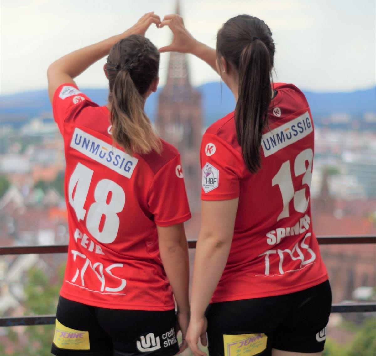 Zwei Spielerinnen vom HSG Freiburg zeigen ein Herz über der Stadt
