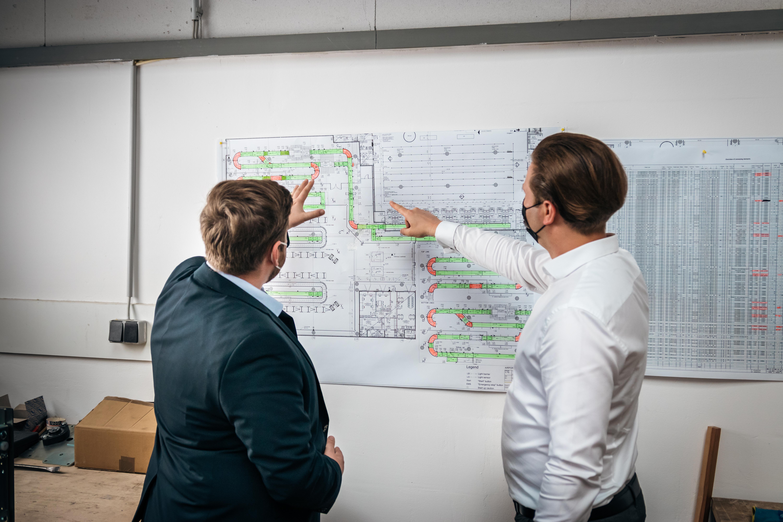 Zwei Männer stehen vor einem Bauplan von SRK Systems