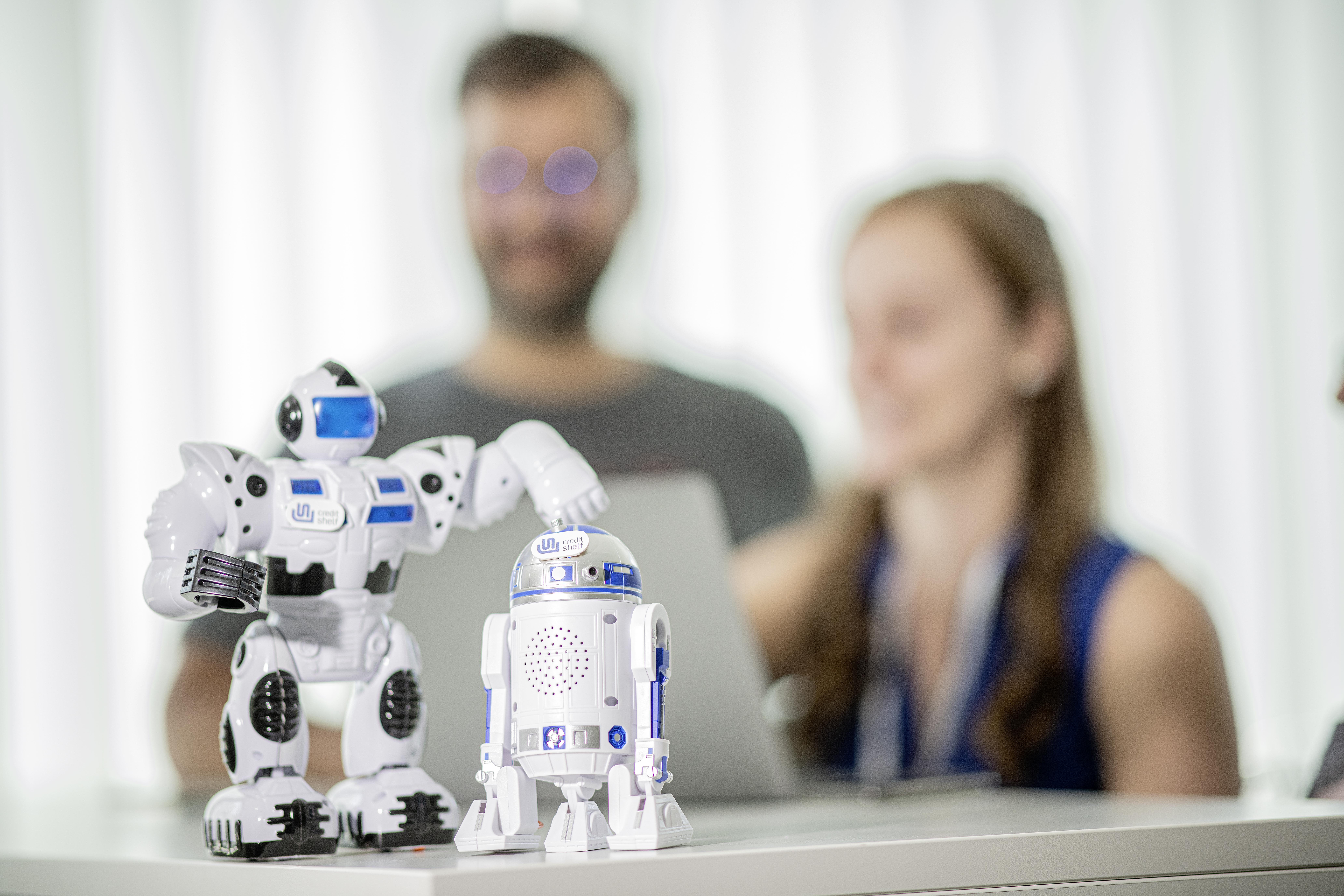 Roboterfiguren im Vordergrund beim Finanzierungsmonitor